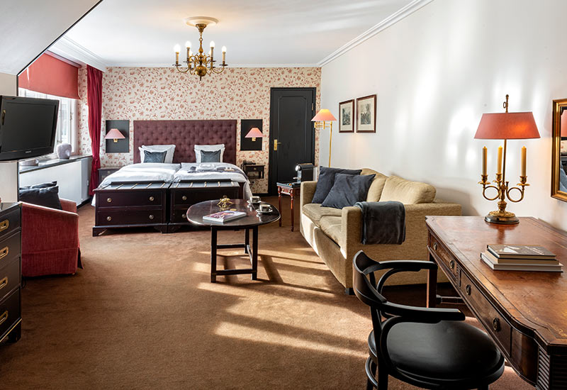 executive deluxe senge med 2 senge og blomstret tapet med to stole sofa og tv